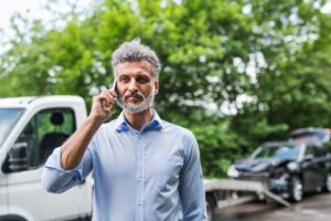 blog post image for can immigrants sue for personal injury damages with photo of mature man making a phone call after a car accident.